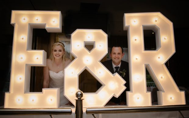 Elaine and Richy's initials go up in florescent lights as the couple enjoy their wedding reception in the Abbey Hotel, Donegal